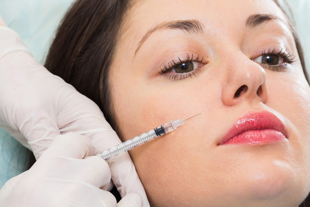 Woman getting Botox on the face by a dermatologist or doctor