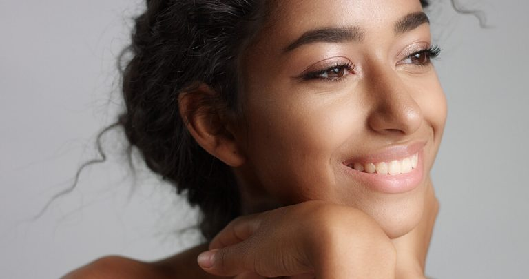 Girl or woman smiling with her hands on her face with clear skin